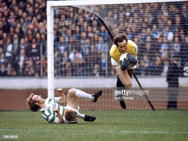 circa 1979 Scottish Football Rangers goalkeeper Peter McCloy leaps through the air to take the ball past Celtic's grounded Johnnie Doyle
