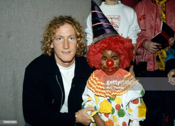 Circa 1990, Arsenal midfielder Ray Parlour at a children's party with a child dressed as a clown