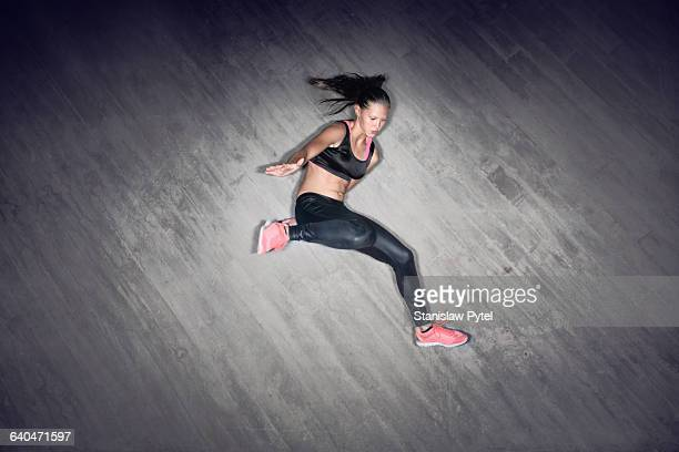 Sport girl jumping against gray wall