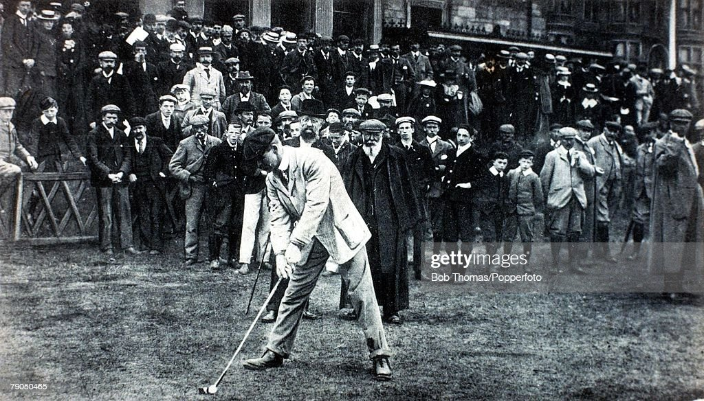 Sport. Golf. The British Open Championships. 1900. St. Andrews, Scotland. Great Britain's J.H.(John Henry) Taylor prepares to drive off from the tee, as the legendary Tom Morris,(with beard and long coat) watches from behind. Taylor went on to win the Cha : News Photo