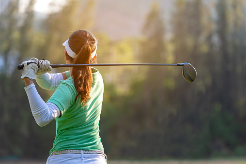 Sport Healthy. Asian sporty woman golf player doing golf swing tee off on the green sunset evening time, she presumably does exercise. Healthy and Lifestyle Concept. 1148397884