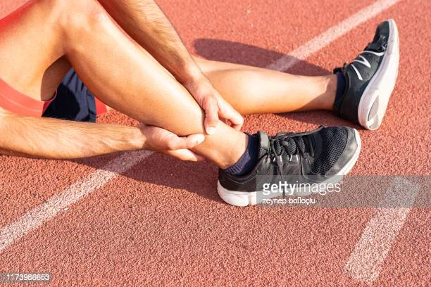 sport injury, a man has ankle pain during outdoor exercise. knee injuries - tendon stock pictures, royalty-free photos & images