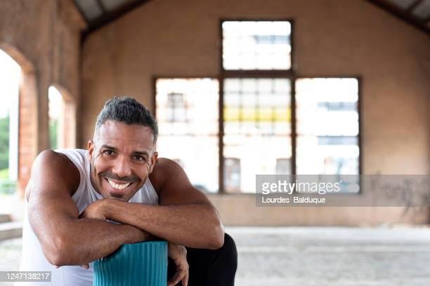 sport man in the street with yoga mat - yoga teacher stock pictures, royalty-free photos & images