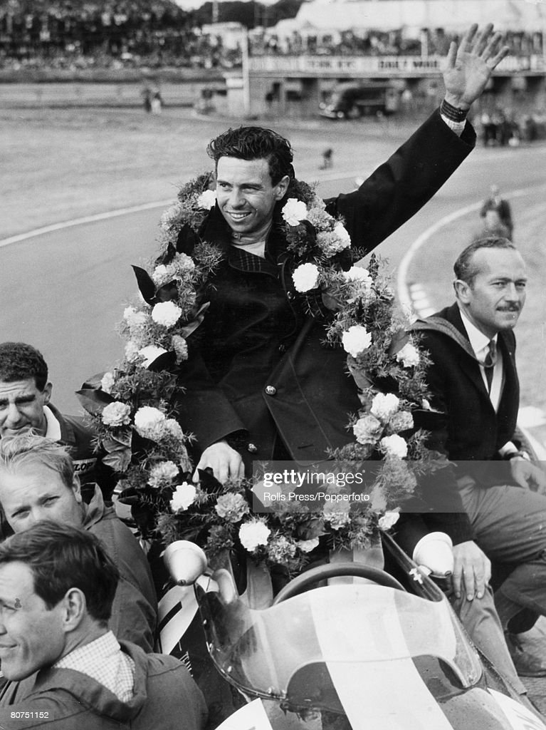 Sport Motor Racing. July 1964. Brands Hatch, England. Racing driver Jim Clark with his armed raised celebrates victory in the British European Auto Racing Grand Prix. World Champion Clark sits in his Lotus Climax car. : News Photo