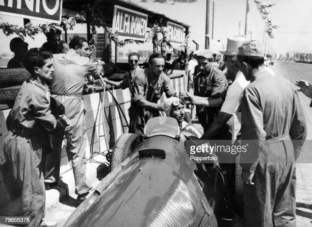 1950 Bari Italy Argentinian Grand Prix driver Juan Manuel Fangio is attended to by Alfa Romeo mechanics as he refuels during the 'Gran Premio Di...