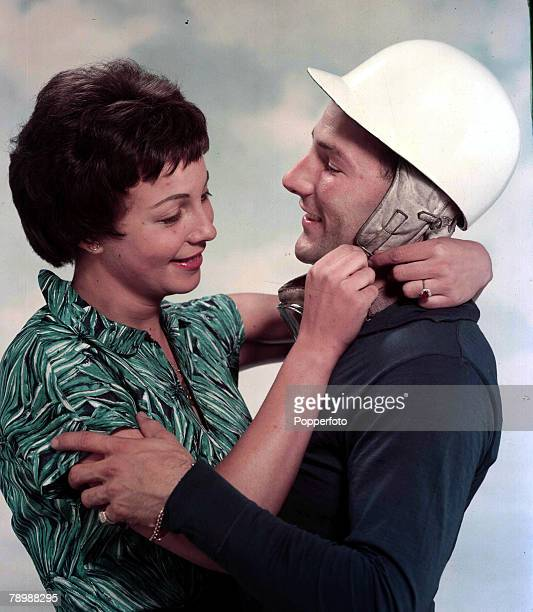 Sport Motor RacingBritish racing driver Stirling Moss with his fiancee Katie Molson who is helping with his crash helmet 1957