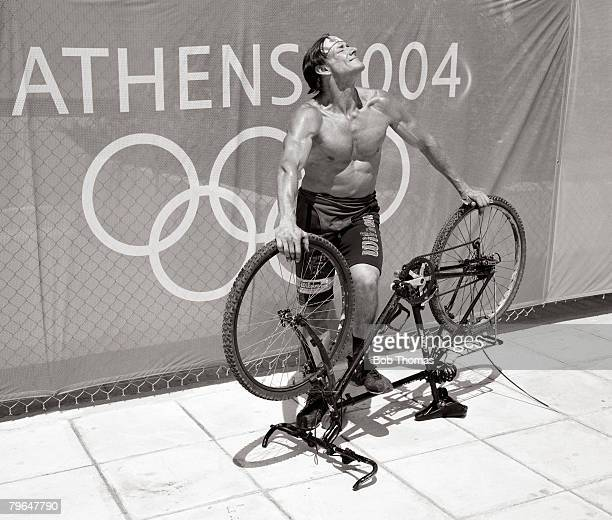 Sport Olympic Games Athens Greece August 2004 A bare chested spectator poses while supporting his upturned bicycle in front of a banner showing the...