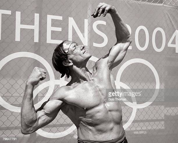 Sport Olympic Games Athens Greece August 2004 A bare chested spectator poses by flexing his muscles in front of a banner showing the Olympic Rings...