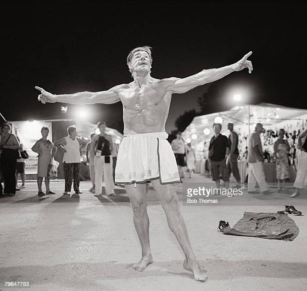Sport, Olympic Games, Athens, Greece, August 2004, A bare chested street entertainer with arms out stretched is surrounded by spectators