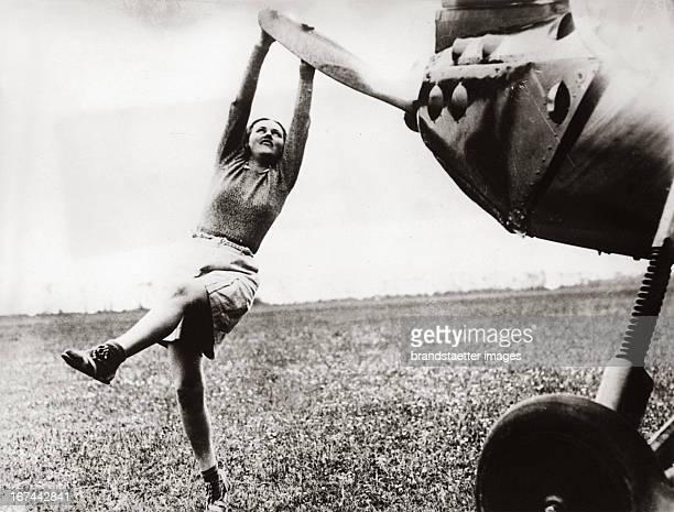 A sport pilot sets a propeller of her aeroplane in motion About 1935 Photograph Sportfliegerin setzt in Brighton/England den Propeller ihres...