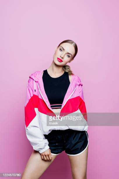 sport portrait of cheerful woman in tracksuit against pink background - fashion model stock pictures, royalty-free photos & images