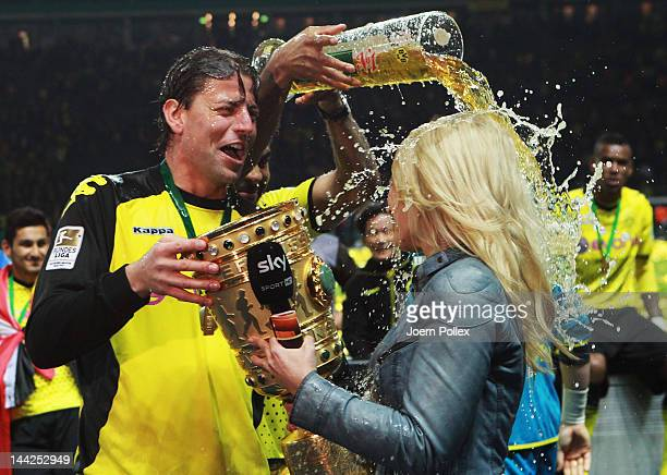 Sport reporter Jessica Kastrop of sky television channel gets a beer shower from Mitchell Langerak after the DFB Cup final match between Borussia...