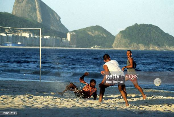 Sport Rio de Janeiro Brazil Young men playing football on the beach with the city and Sugarloaf mountain in the background