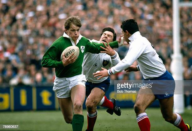 21st March 1987 5 Nations Championship in Dublin Ireland 13 v France 19 Ireland wing Trevor Ringland hands off French defenders Franck Mesnel centre...