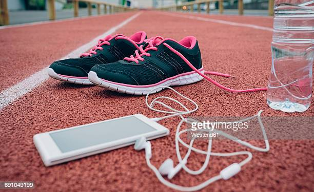 Sport shoes, smartphone with earbuds and bottle of water on tartan track