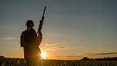 Sport shooting and hunting - woman with a rifle at sunset