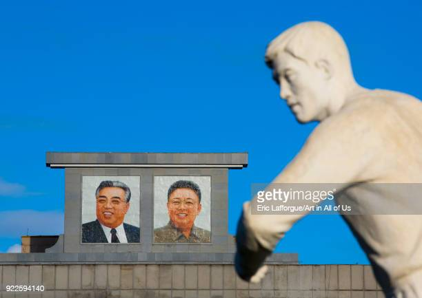 Sport statue in front of Kim il Sung and Kim Jong il portraits Pyongan Province Pyongyang North Korea on September 8 2012 in Pyongyang North Korea