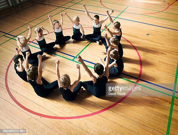 Sport team (7-9) sitting in circle in gym, arms raised