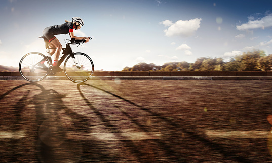 Sport. The cyclist rides on his bike at sunset. Dramatic background. 825604116