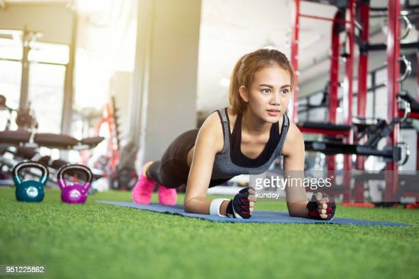 sport woman working out in gym. - asian six pack stock photos and pictures