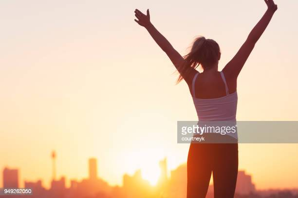 sport women celebrating with arms raised. - wellbeing stock pictures, royalty-free photos & images