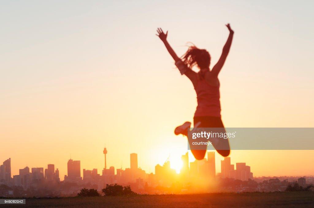 スポーツ女性ジャンプと腕を上げると祝います。 : ストックフォト
