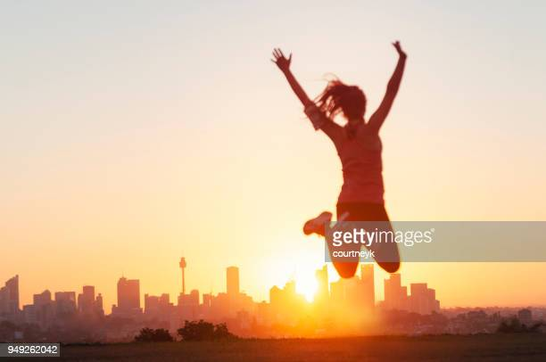 sport women jumping and celebrating with arms raised. - joy stock pictures, royalty-free photos & images