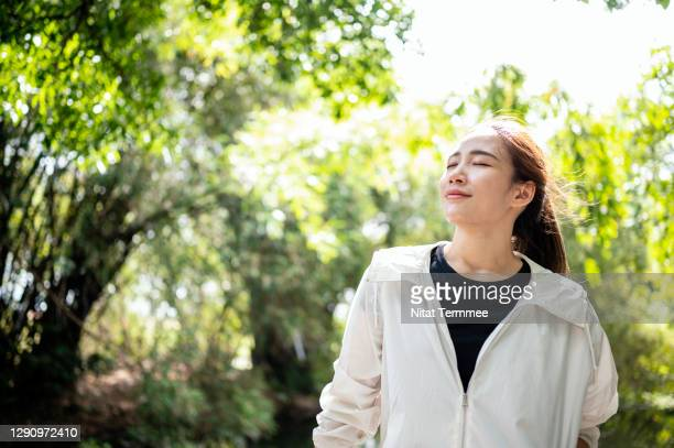 sport women relaxing outdoor after workout in a city park. - buddhism stock pictures, royalty-free photos & images