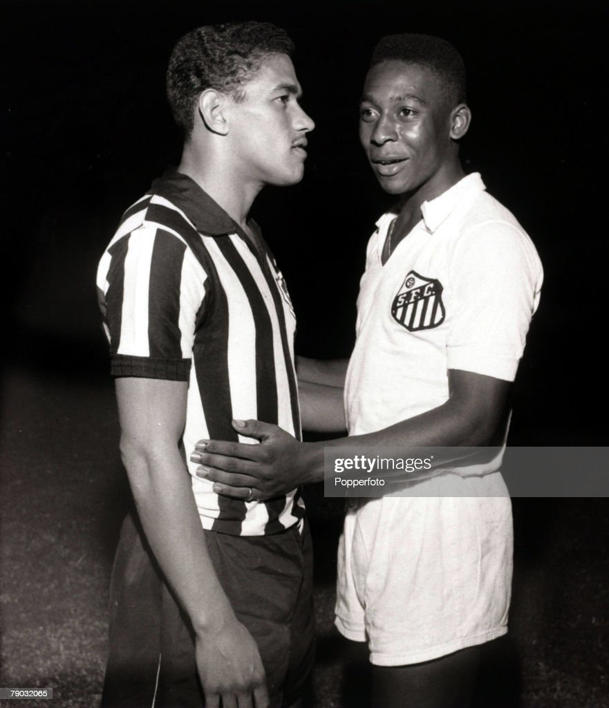 Sport/Football in South America. 1959. Brazilian international players Garrincha and Pele (right) are pictured in friendly opposition as they prepare for a club game, Garrincha in the stripes of Botafogo and Pele for Santos. : News Photo