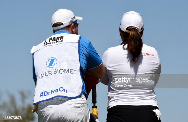 Sporting a bib with the 'Drive On' motto on it the caddie for Inbee Park of Korea wait to hit on the third hole tee box during the final round of the...