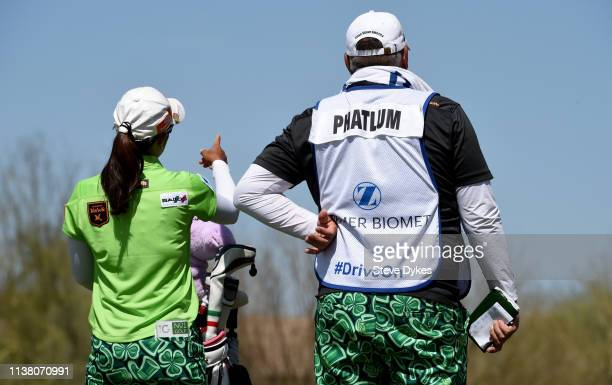 Sporting a bib with the 'Drive On' motto on it the caddie for Pornanong Phatlum of Thailand and Pornanong wait to hit on the third hole tee box...
