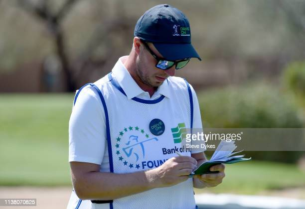 Sporting a hat and a button with the 'Drive On' motto on it the caddie for Nanna Koertz Madsen check the yardage on the third hole tee box during the...