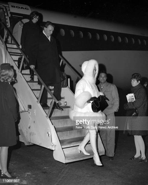 Sporting a Hip Outfit outfitted in white leather hiphigh boots with a white threequarter length ermine coat and matching hood Elizabeth Taylor...