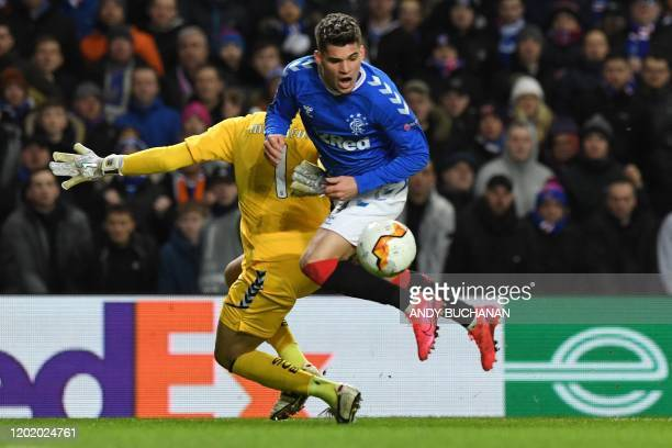 Sporting Braga's Brazilian goalkeeper Matheus Magalhaes clashes with Rangers' Romanian midfielder Ianis Hagi during the UEFA Europa League round of...