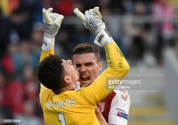 Sporting Braga's Brazilian goalkeeper Matheus Magalhaes is congratulated by teammate Portuguese midfielder Joao Palhinha for stopping a penalty kick...