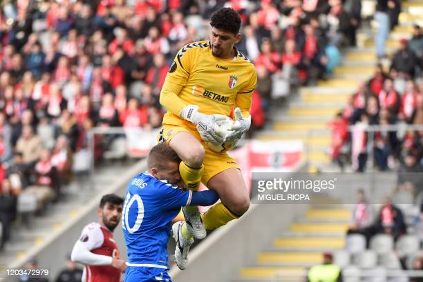 Sporting Braga's Brazilian goalkeeper Matheus Magalhaes jumps over Rangers' Northern Irish midfielder Steven Davis during the UEFA Europa League...