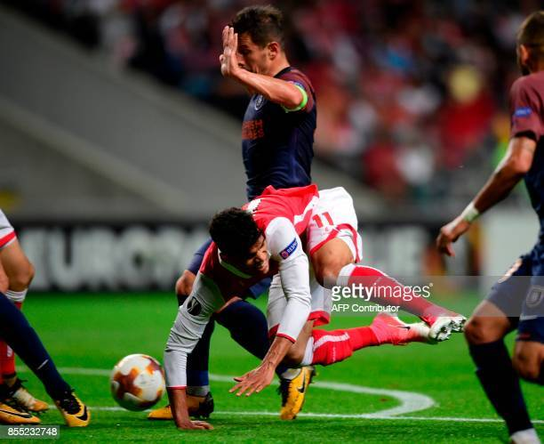 Sporting Braga's Brazilian midfielder Danilo Silva falls next to Basaksehir's midfielder Emre Belozoglu during the UEFA Europa league football match...