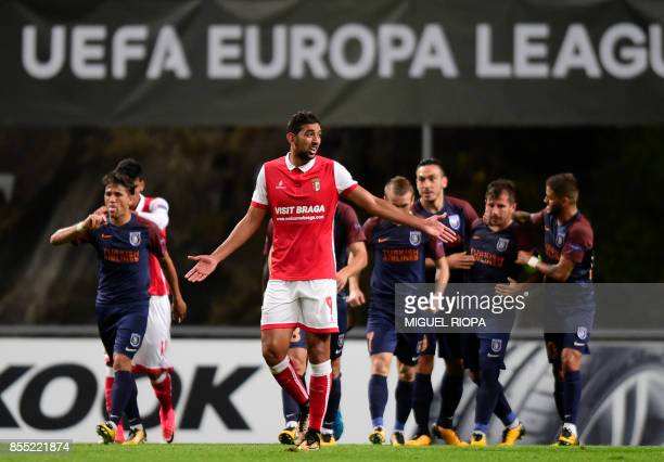 Sporting Braga's Egyptian forward Ahmed Hassan reacts as Basaksehir's players celebrate a goal scored by bBasaksehir's midfielder Emre Belozoglu...