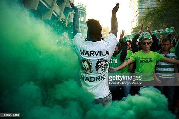 Sporting Clube de Portugal fan encourages his mates surrounded by the smoke of a green flare before the UEFA Champions League group stage match...