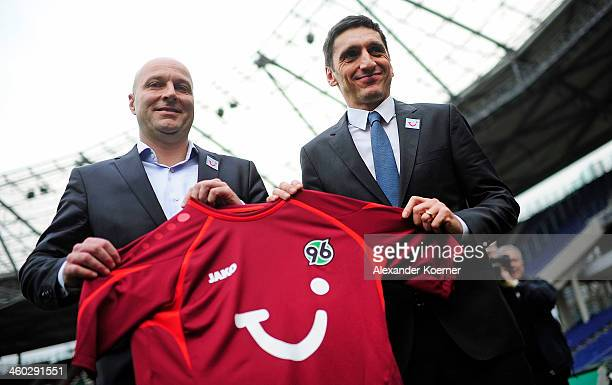 Sporting director Dirk Dufner and new head coach Tayfun Korkut hold together a soccer Jersey of Bundesliga Club Hannover during a Press Conference as...