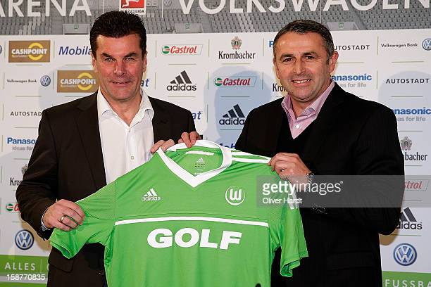 Sporting director Klaus Allofs of Vfl Wolfsburg presents a team jersey to new head coach Dieter Hecking during a press conference at Volkswagen Arena...