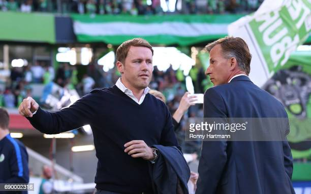 Sporting director Olaf Rebbe of Wolfsburg chats with head coach Andries Jonker of Wolfsburg prior to the Bundesliga Playoff first leg match between...