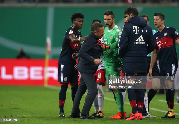 Sporting director Ralf Rangnick of Leipzig argues with David Alaba and goalkeeper Sven Ulreich of Muenchen during the DFB Cup match between RB...