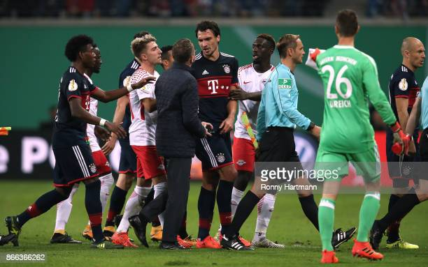Sporting director Ralf Rangnick of Leipzig argues with Mats Hummels of Muenchen during the DFB Cup match between RB Leipzig and Bayern Muenchen at...