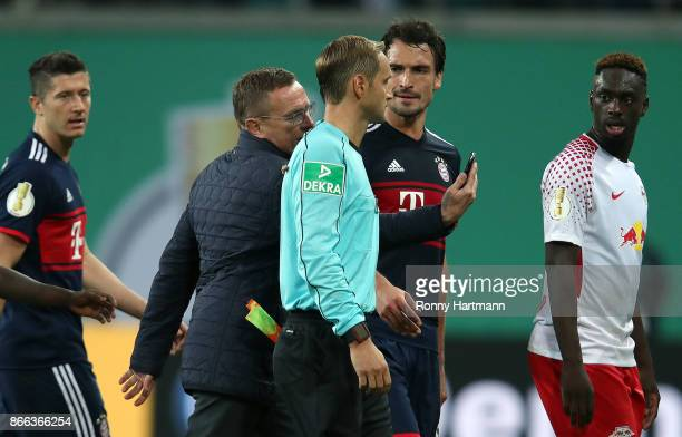 Sporting director Ralf Rangnick of Leipzig shows his smartphone to Mats Hummels of Muenchen and the assistant referee Arno Blos during the DFB Cup...