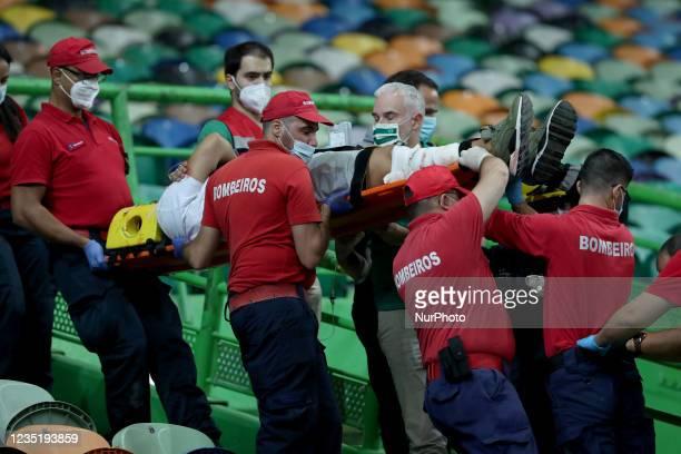 Sporting fan is taken out on a stretcher by firefighters after falling from the top stand during the Portuguese League football match between...