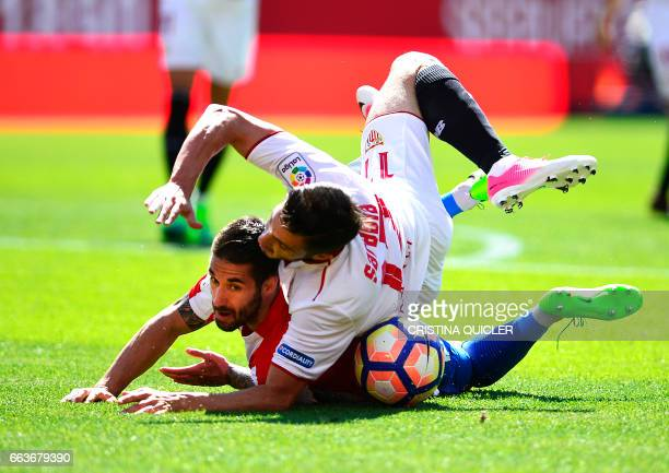 TOPSHOT Sporting Gijon's defender Lillo Castellano fights for the ball with Sevilla's midfielder Pablo Sarabia during the Spanish league football...