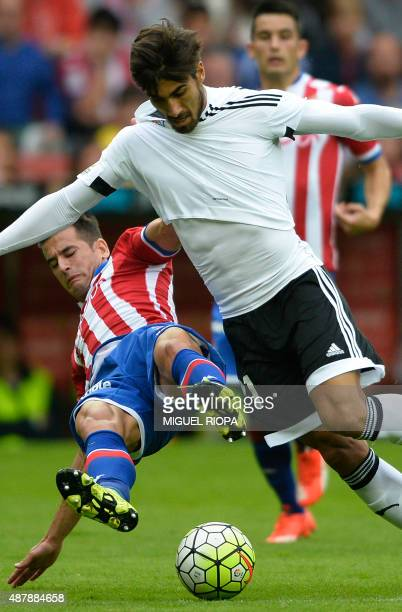 Sporting Gijon's defender Luis Hernandez vies with Valencia's Portuguese midfielder Andre Gomes during the Spanish league football match Real...
