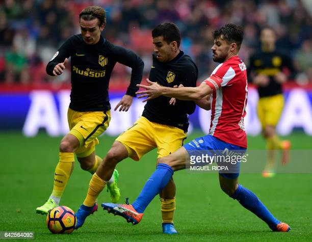 Sporting Gijon's defender Roberto Canella vies with Atletico Madrid's French forward Antoine Griezmann and Argentinian midfielder Angel Correa during...