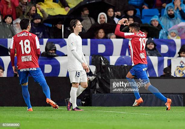 Sporting Gijon's midfielder Carlos Carmona celebrates a goal beside Real Madrid's Croatian midfielder Luka Modric during the Spanish league football...